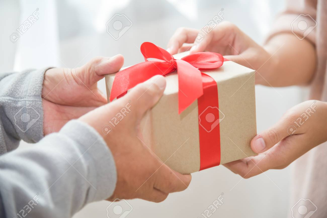 Closeup On Hands Asian Woman Giving A Brown Gift Box To Elderly Man For Birthday