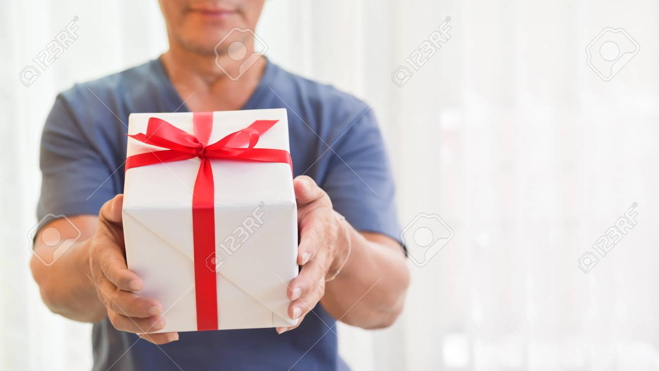 Happy Asian Elderly Man Standing And Holding A White Gift Box On Background Birthday