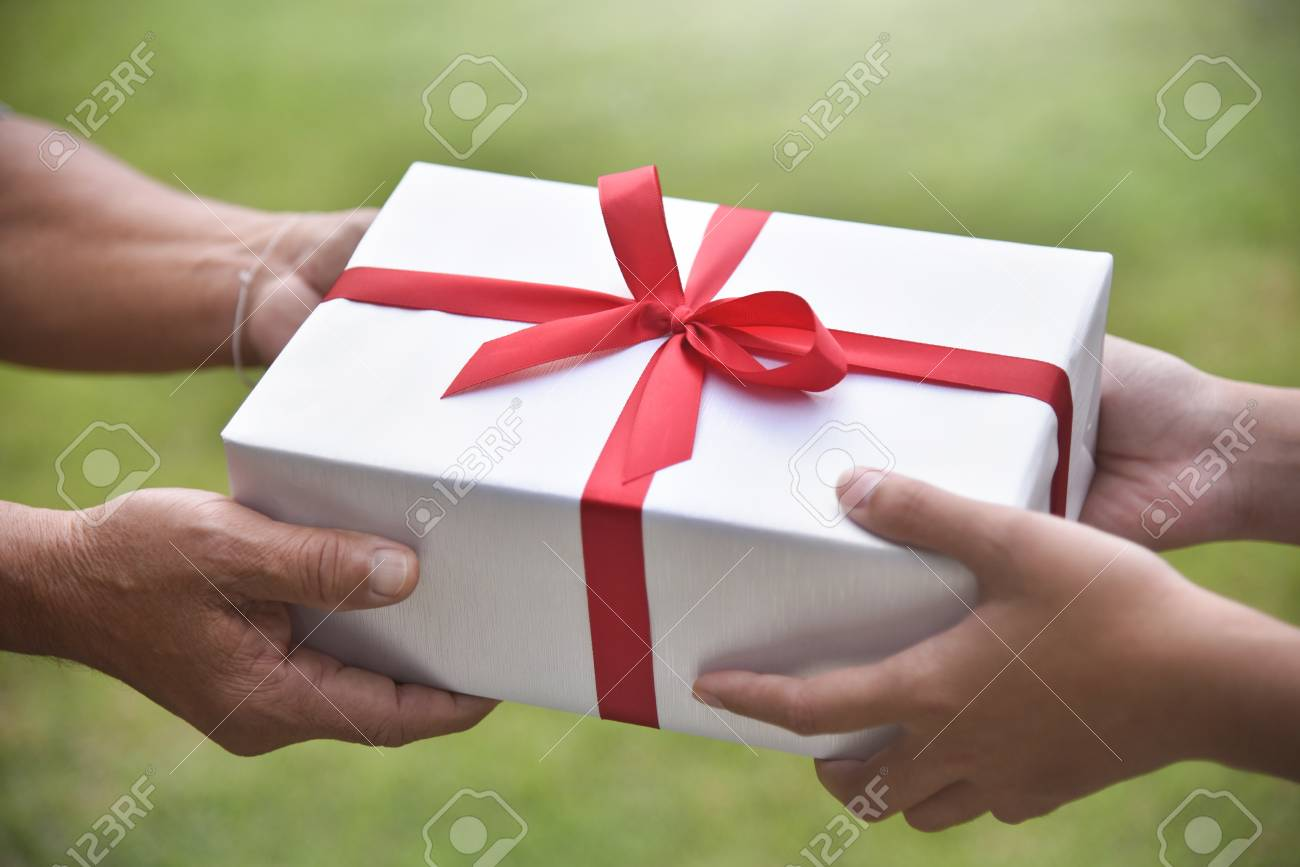 Closeup On Hands Asian Woman Giving A White Gift Box To Elderly Man Green Nature