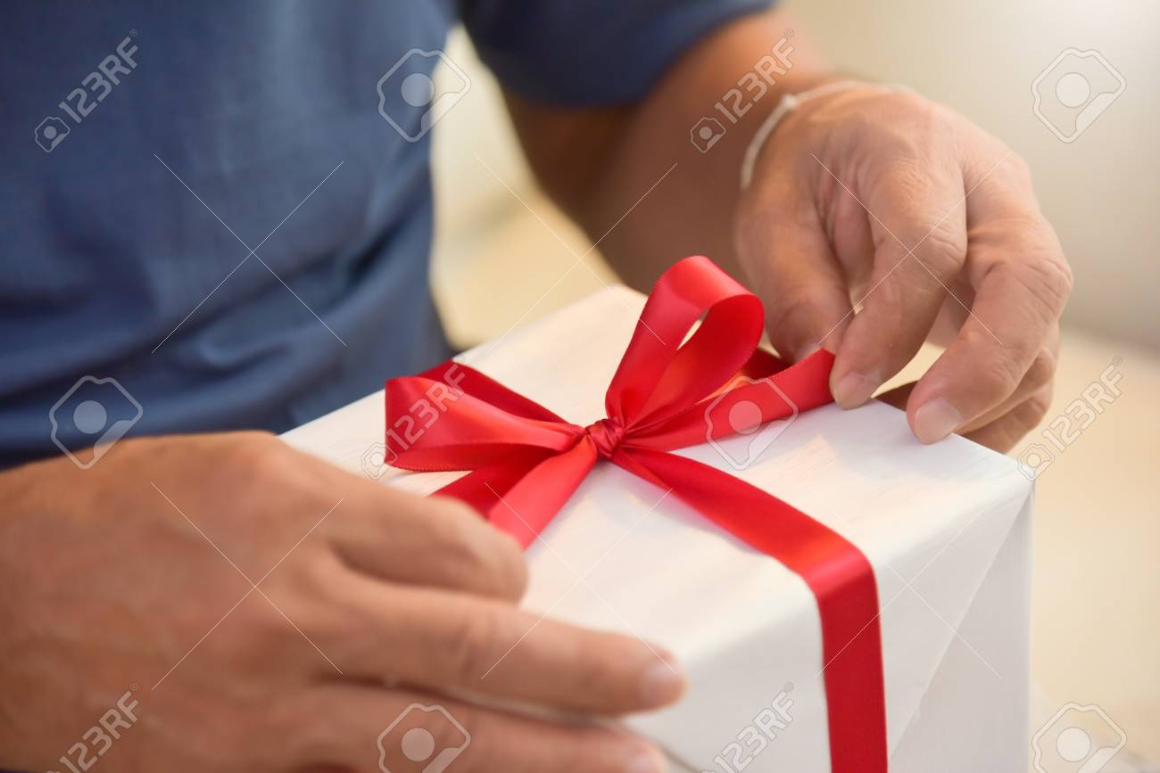 Asian Elderly Man Holding On Red Ribbon Of White Gift Box
