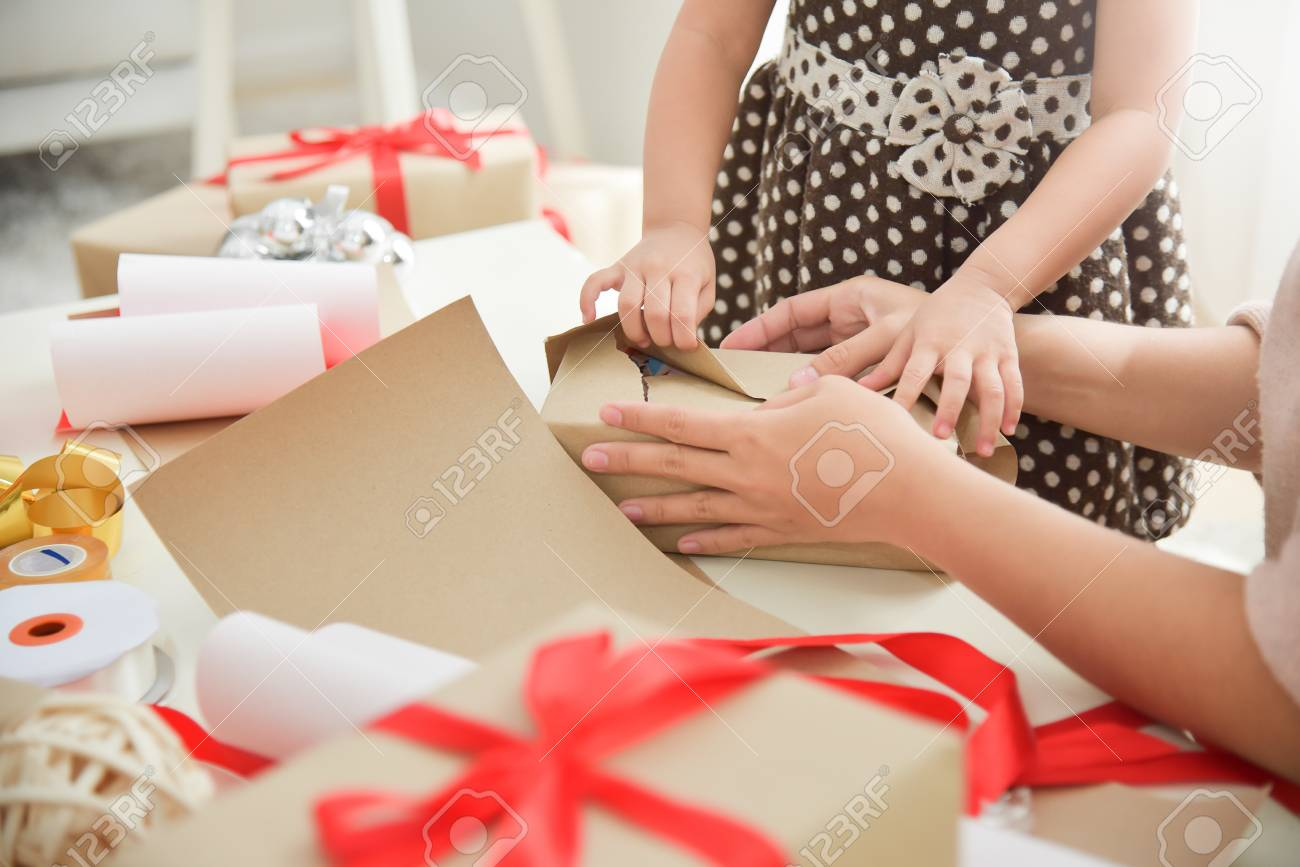 Closeup Young Mother And Her Daughter Hands Wrapping A Gift Box For Birthday Christmas
