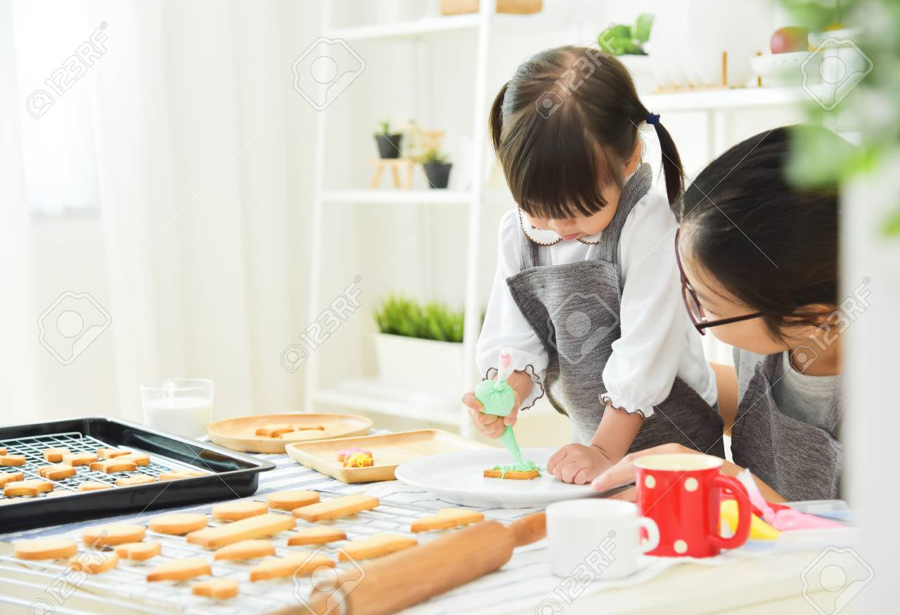 Cabrito Asiático Y Madre Joven Que Adorna Las Galletas En La Cocina ...