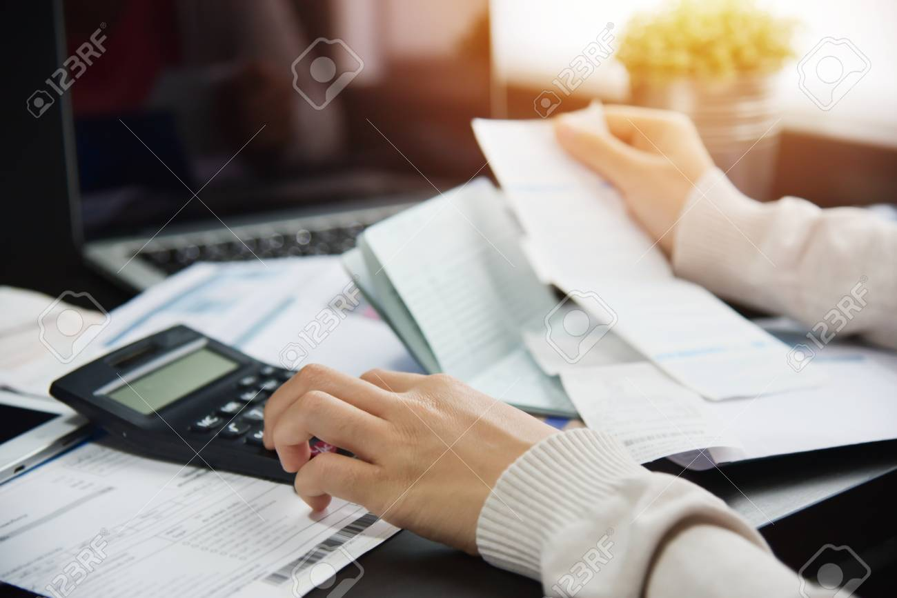 Close up of woman hand calculating her monthly expenses with calculator. Debt. - 101540991
