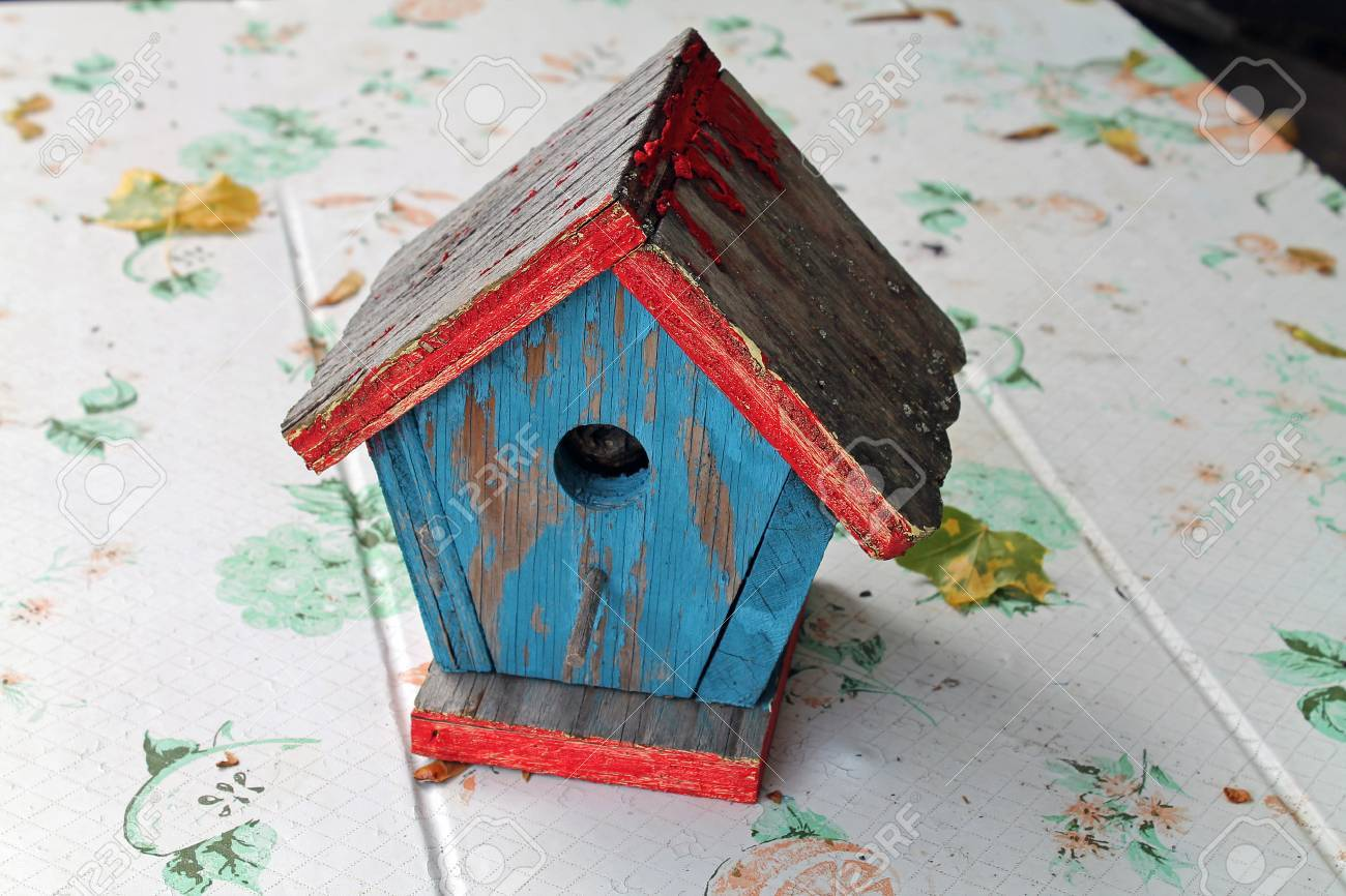 Weathered Wooden Birdhouse With Peeling Red And Blue Paint