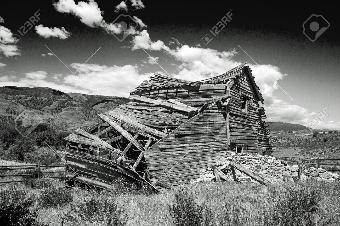 Weathered Old Barn Collapsing Under A Cloudy Sky In Black And