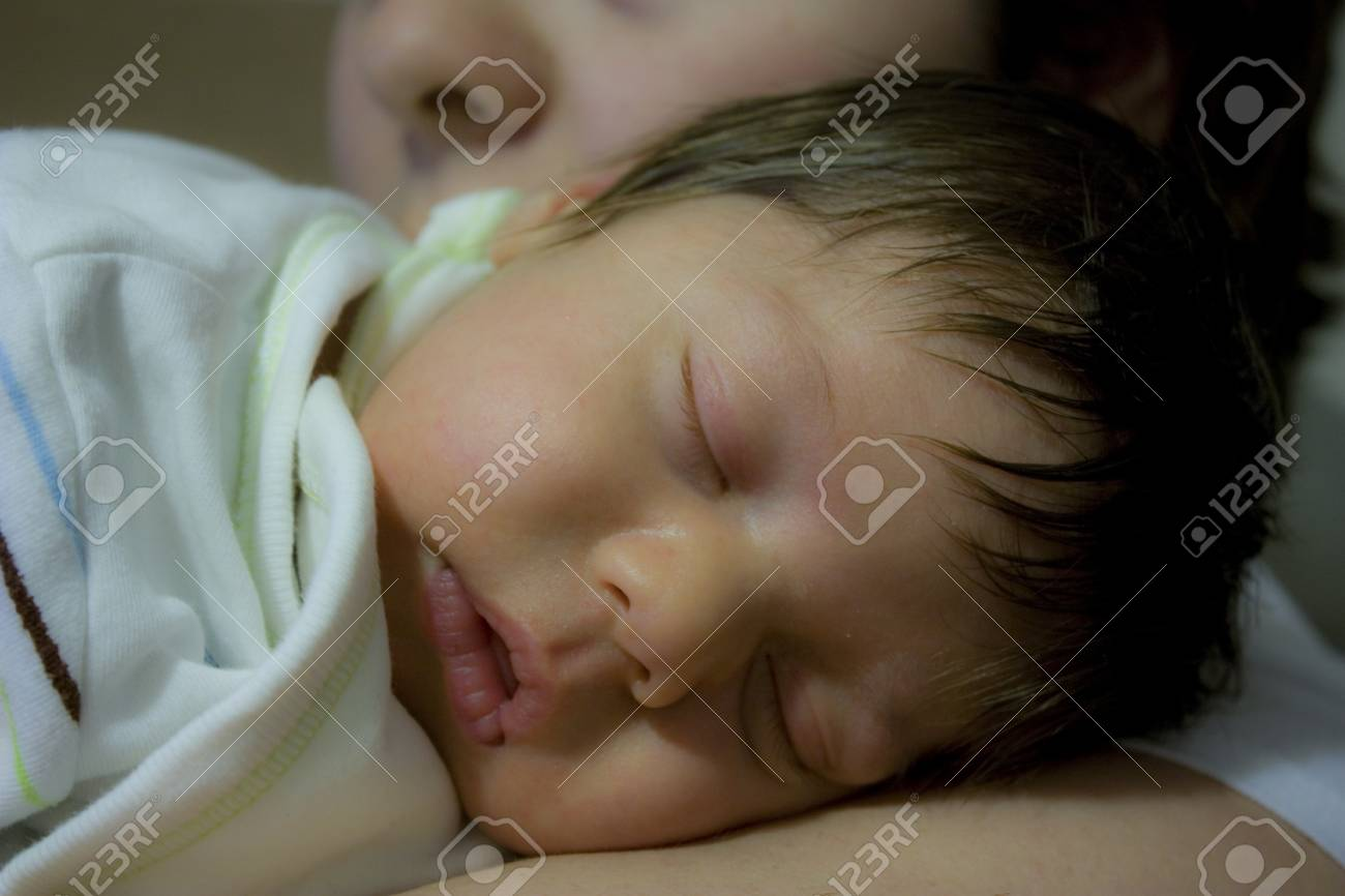 cute sleeping baby in his mothers arms stock photo, picture and