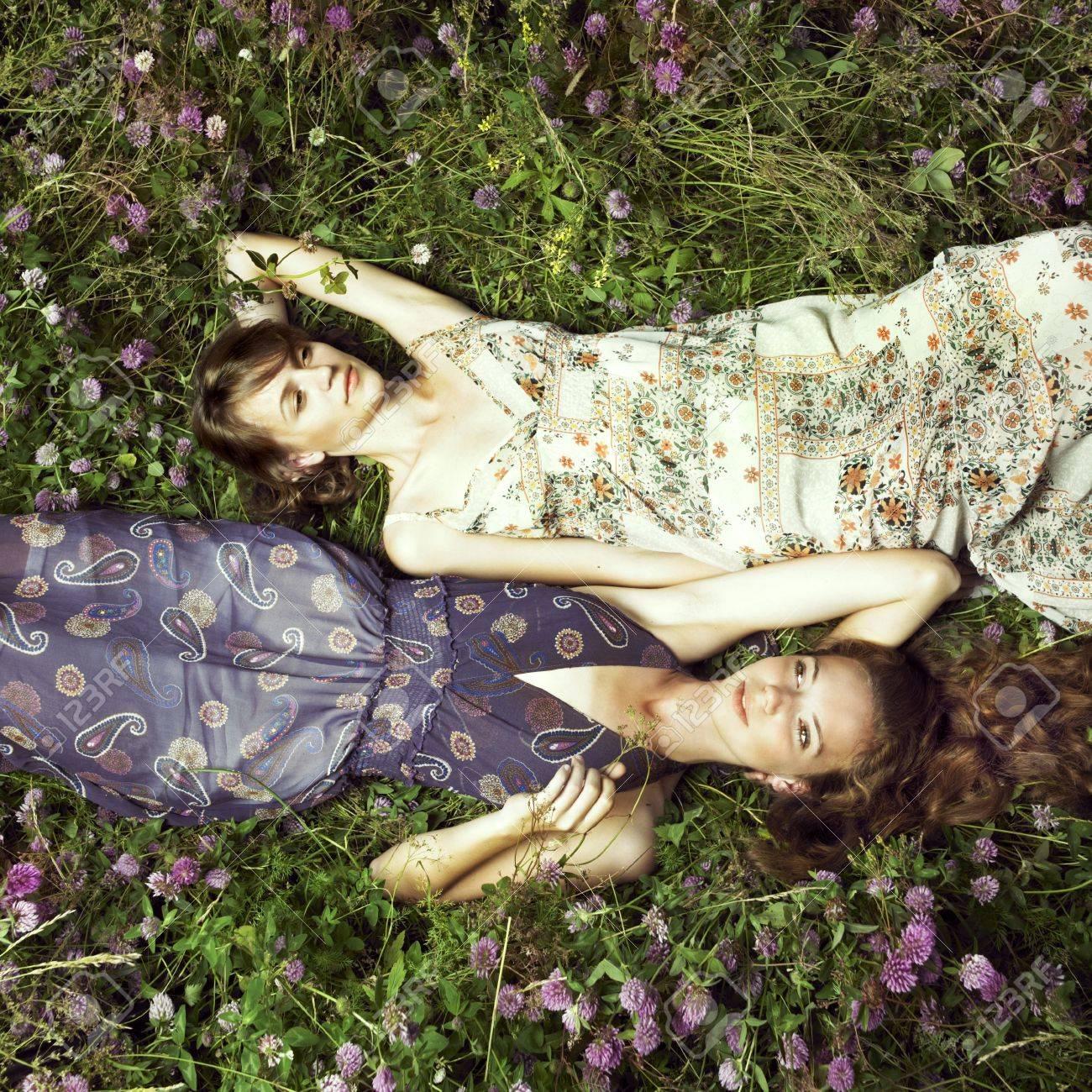 Two romantic girl lying on flower meadow Stock Photo - 7469155