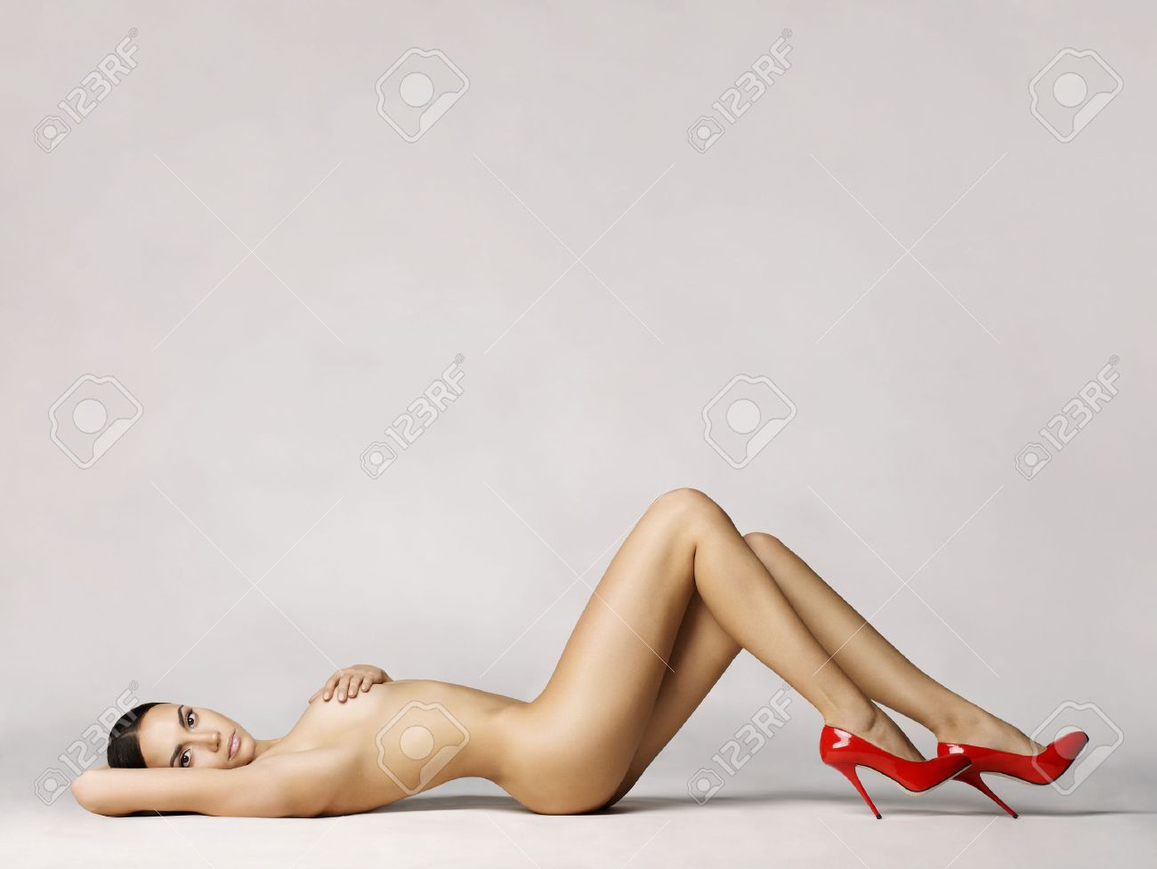 elegant naked woman in red shoes laying on white background Standard-Bild - 34349717