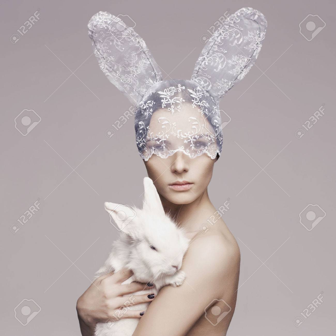 Studio fashion portrait of beautiful lady with white rabbit Standard-Bild - 37379942