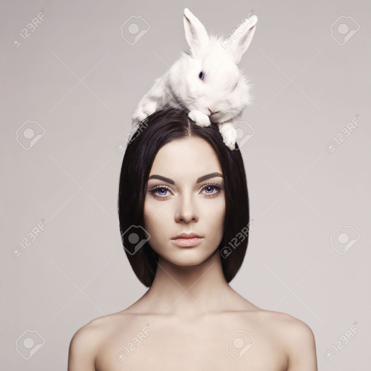 Studio fashion portrait of beautiful lady with white rabbit Standard-Bild - 37489403