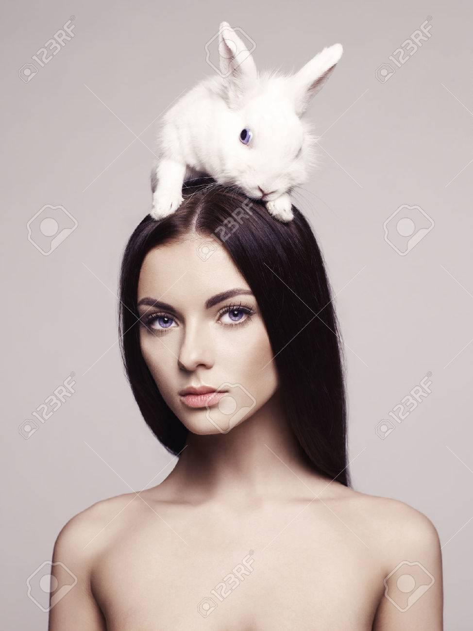 Studio fashion portrait of beautiful lady with white rabbit Standard-Bild - 38252887
