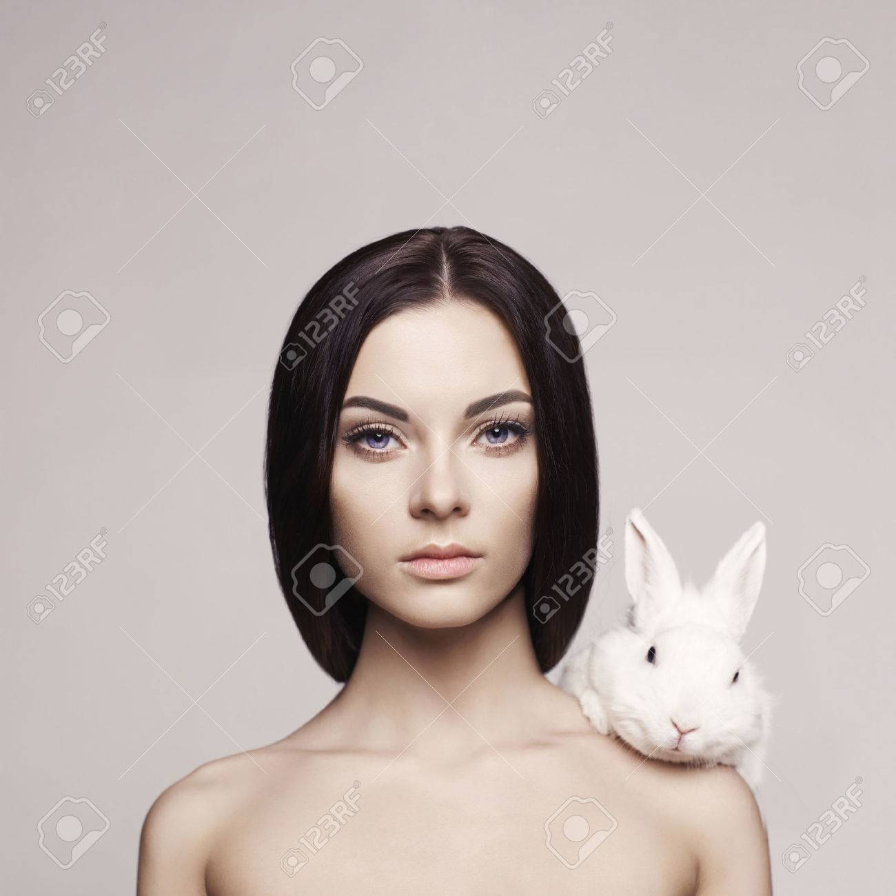 Studio fashion portrait of beautiful lady with white rabbit Standard-Bild - 39969291