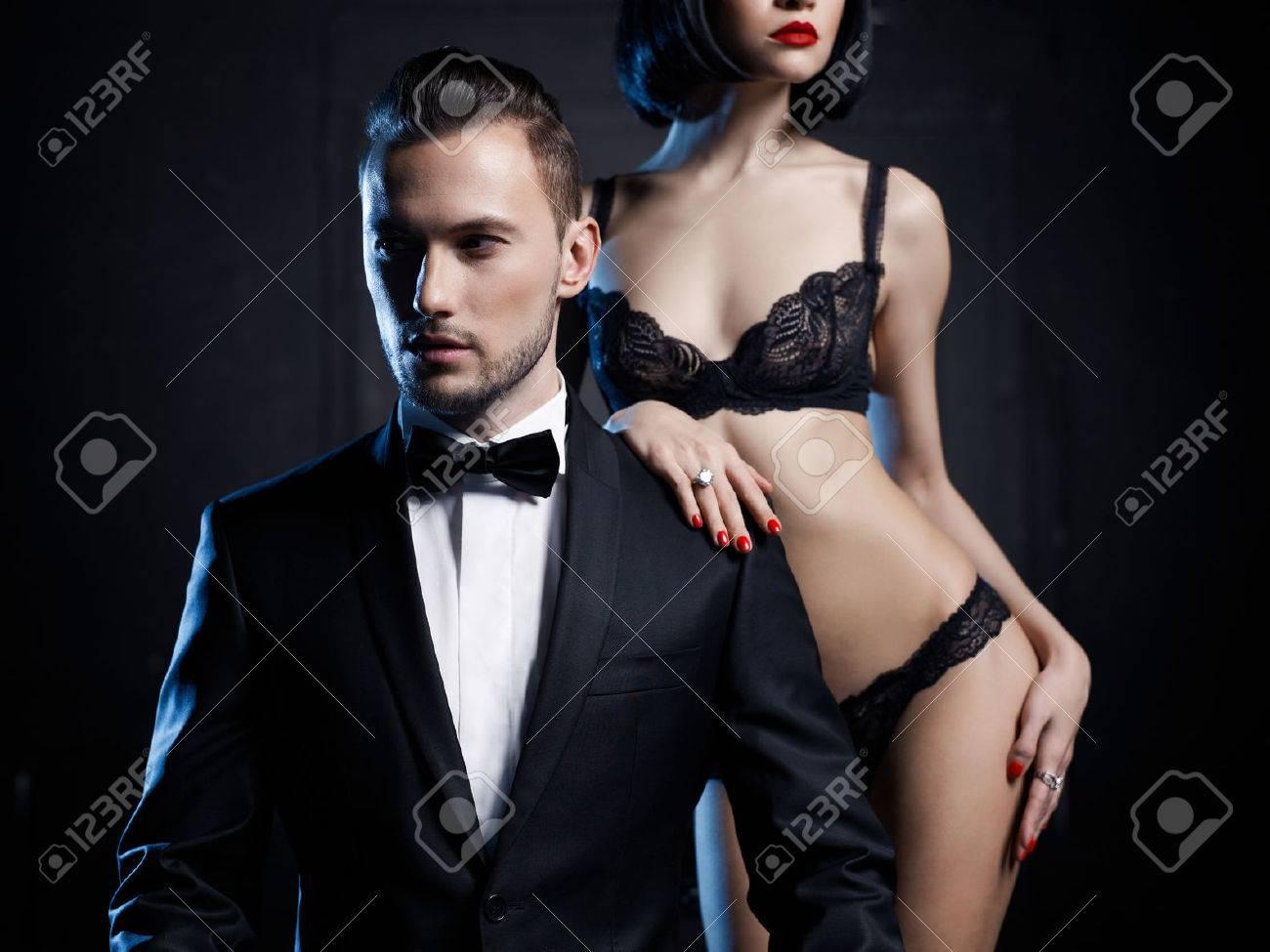 Fashion studio photo of a sensual couple in lingerie and a tuxedo Standard-Bild - 40847929
