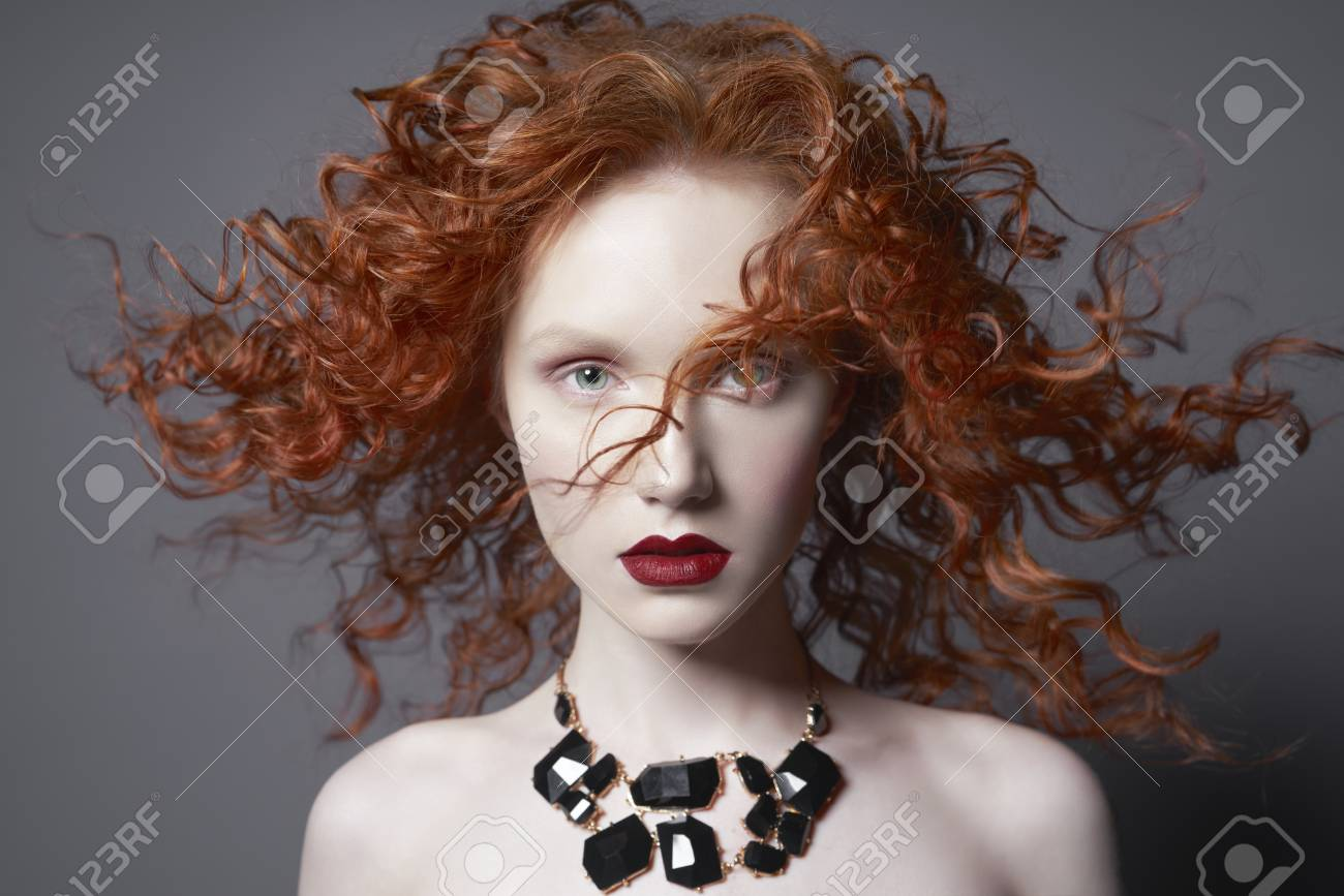 Beautiful Young Woman With Black Jewelry And Red Hair On Grey