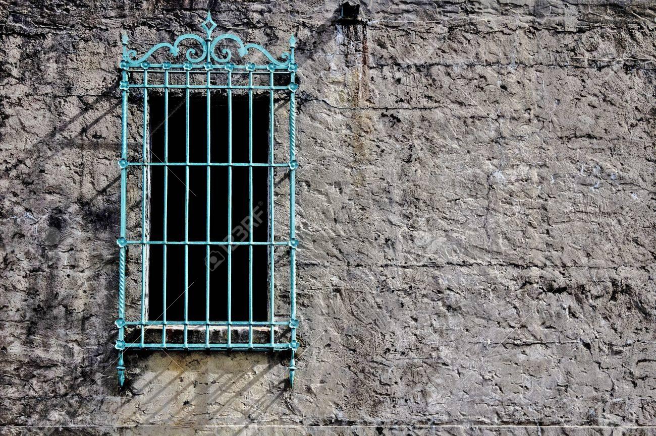 Fenêtre avec grille verte décorative dans le mur de ciment d\u0027un château de  style