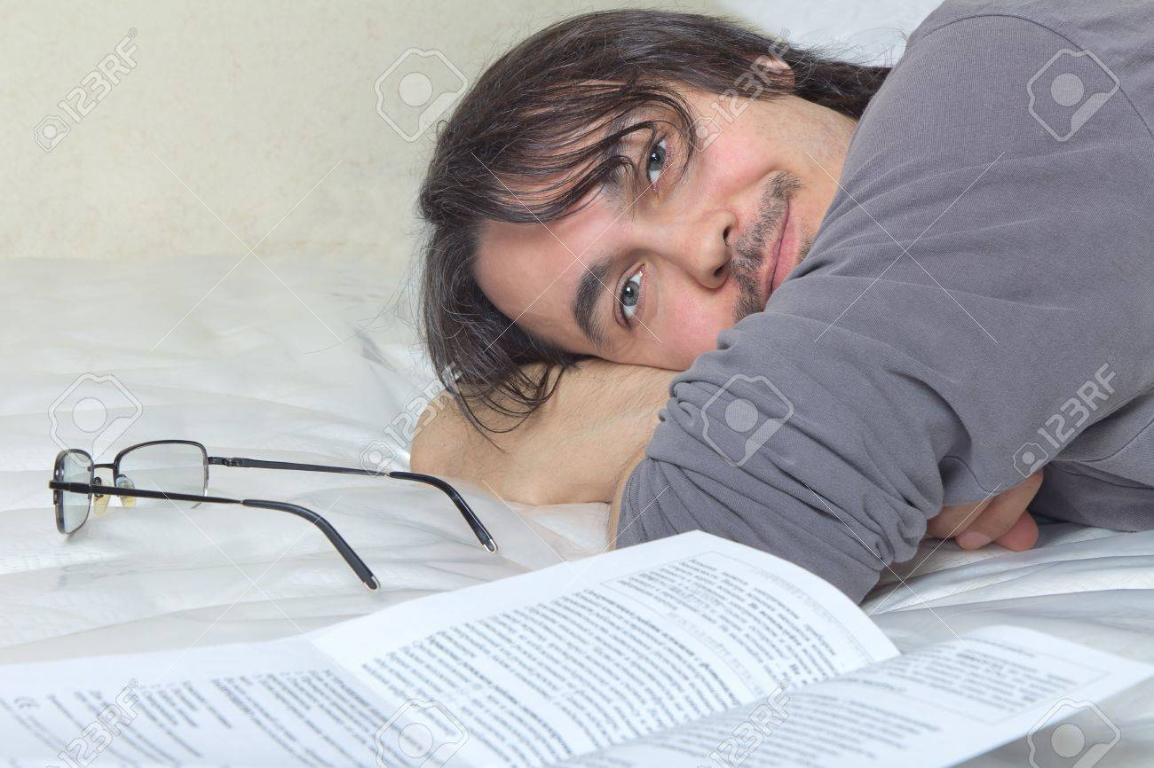 Handsome Caucasian middle aged adult man lying in bed and reading Stock Photo - 13130133