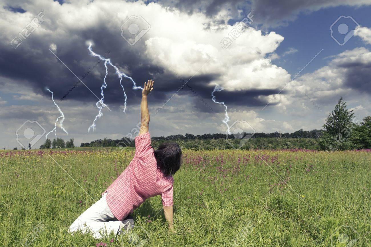 Man stopping thunders and lightning in the field Stock Photo - 14590851