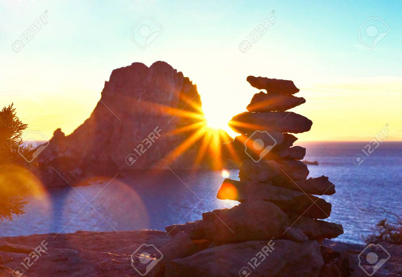Sunset at Es Vedra with sunbeam. Sun shining through a stack rock on ibiza Iceland. - 60596962