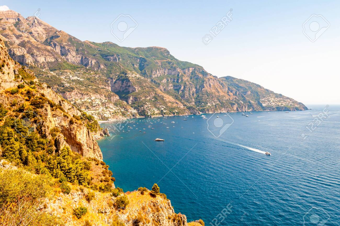Beautiful scenic landscape of Positano, Italy. Rocky coastline full of boats and yachts traveling near high mountains. Cityscape of Positano surrounded by hills and deep blue Tyrrhenian sea waters - 134568559