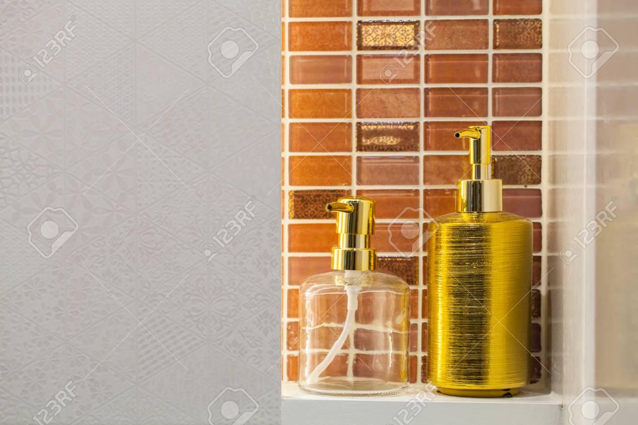 bouteille de savon liquide clair et doré avec fond de carreaux