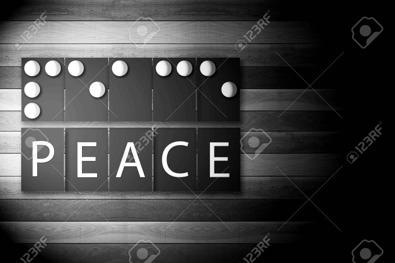 Black and white photo of braille alphabet meaning of peace in bright light on wooden background