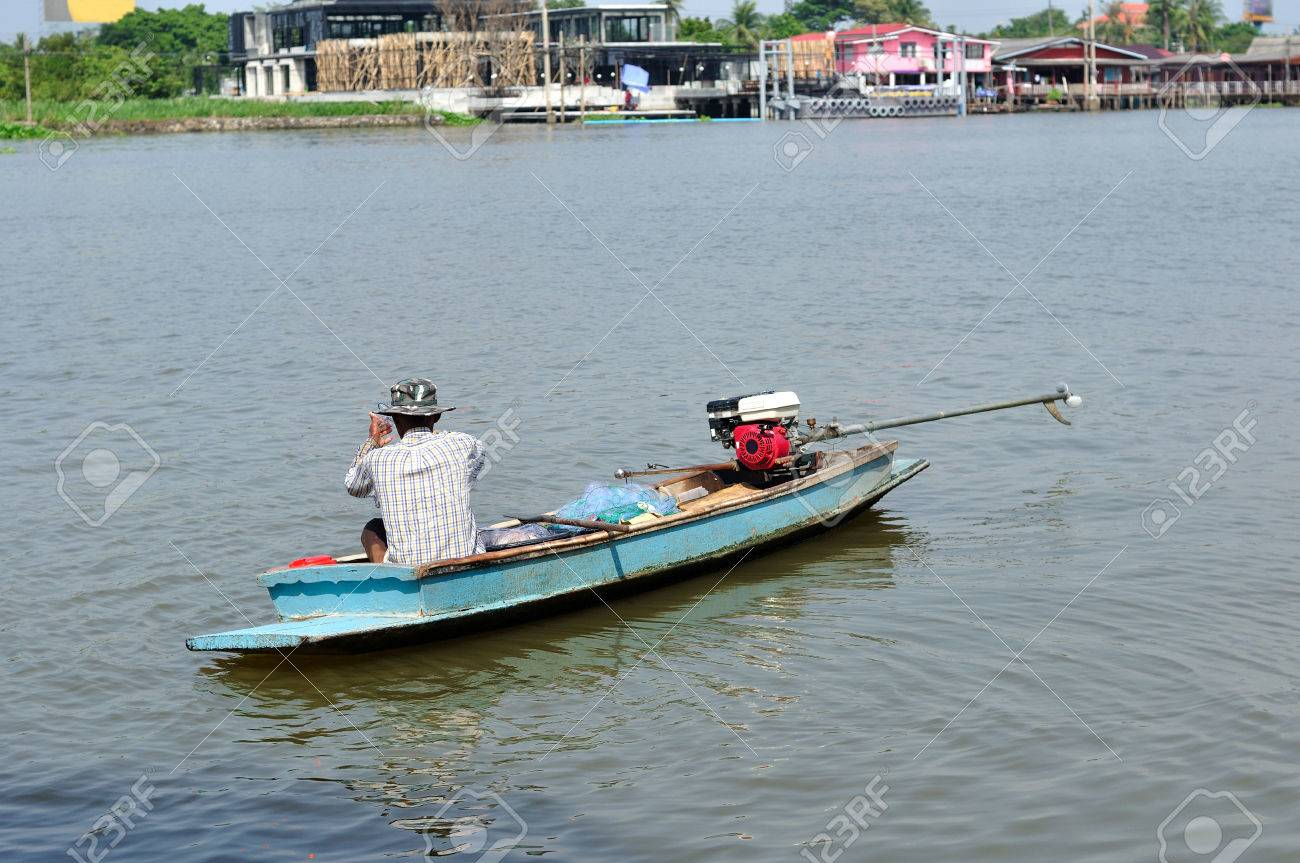 Asian old fisherman catching fish on small long tail-boat Stock Photo -  24121736