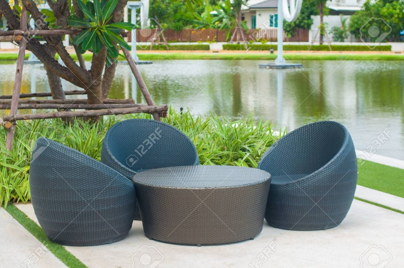 Black outdoor rattan sofa set for rest and relax next to lake..