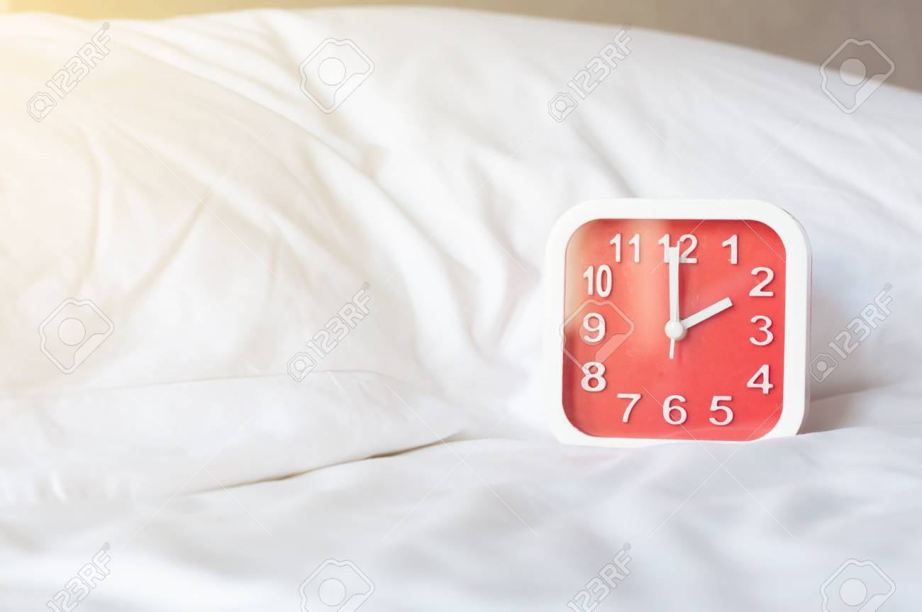 Square red alarm clock on white bed white pillow in bedroom,..