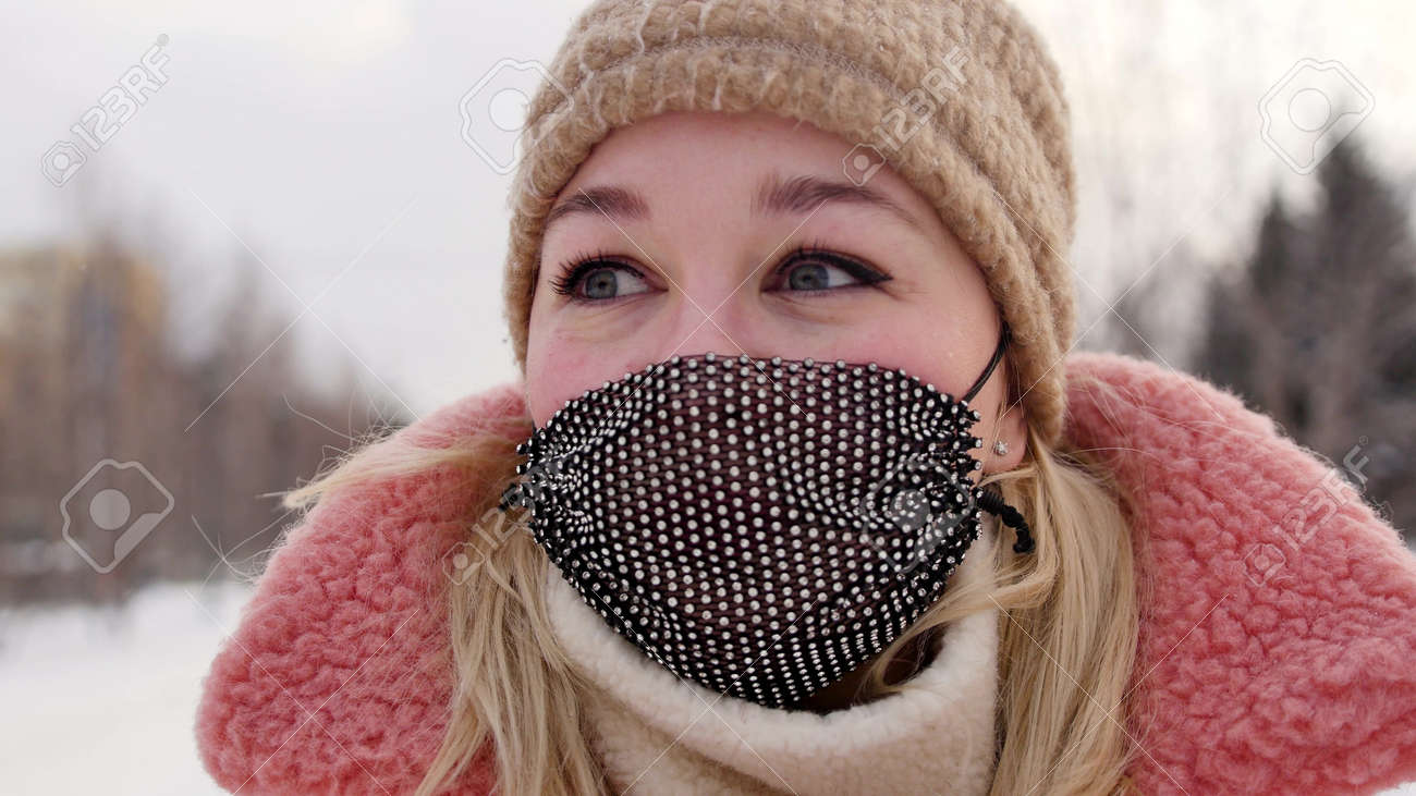 A woman in a coral black mask and a fur hat on a city street in a cold winter. - 165273502