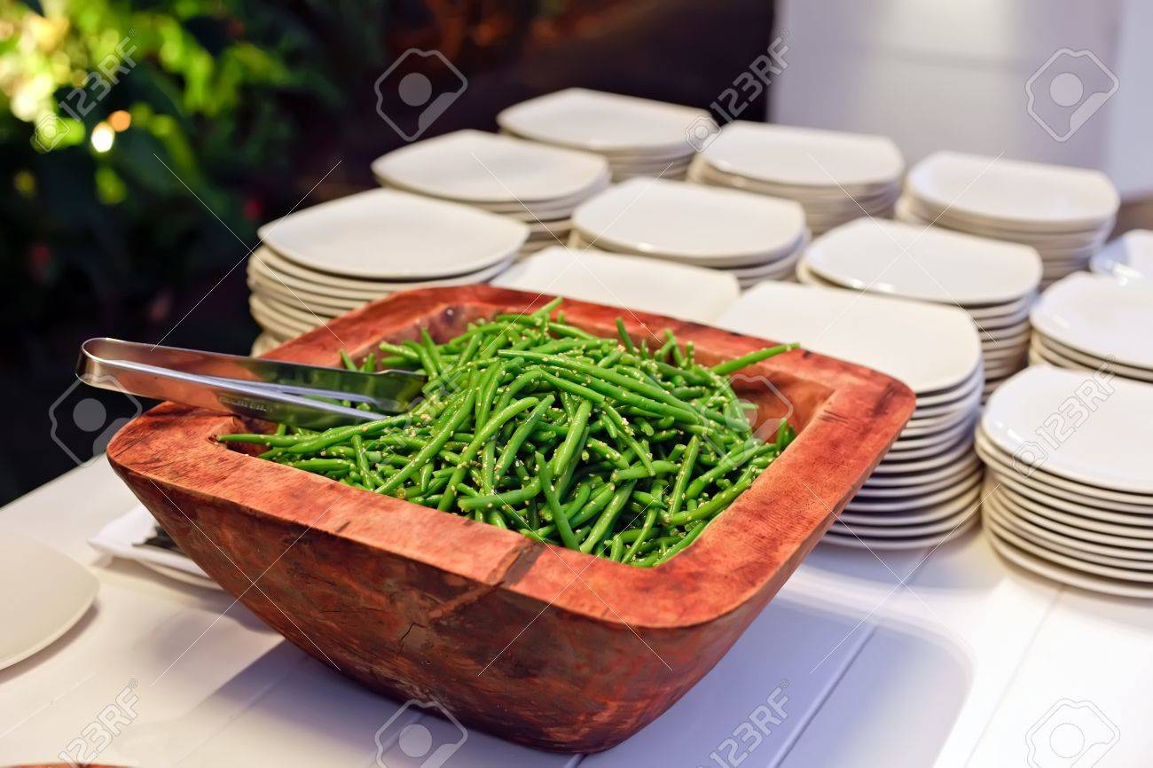 pieces long beans in a wooden bowl on the background of a stack of plates Stock Photo - 12854638