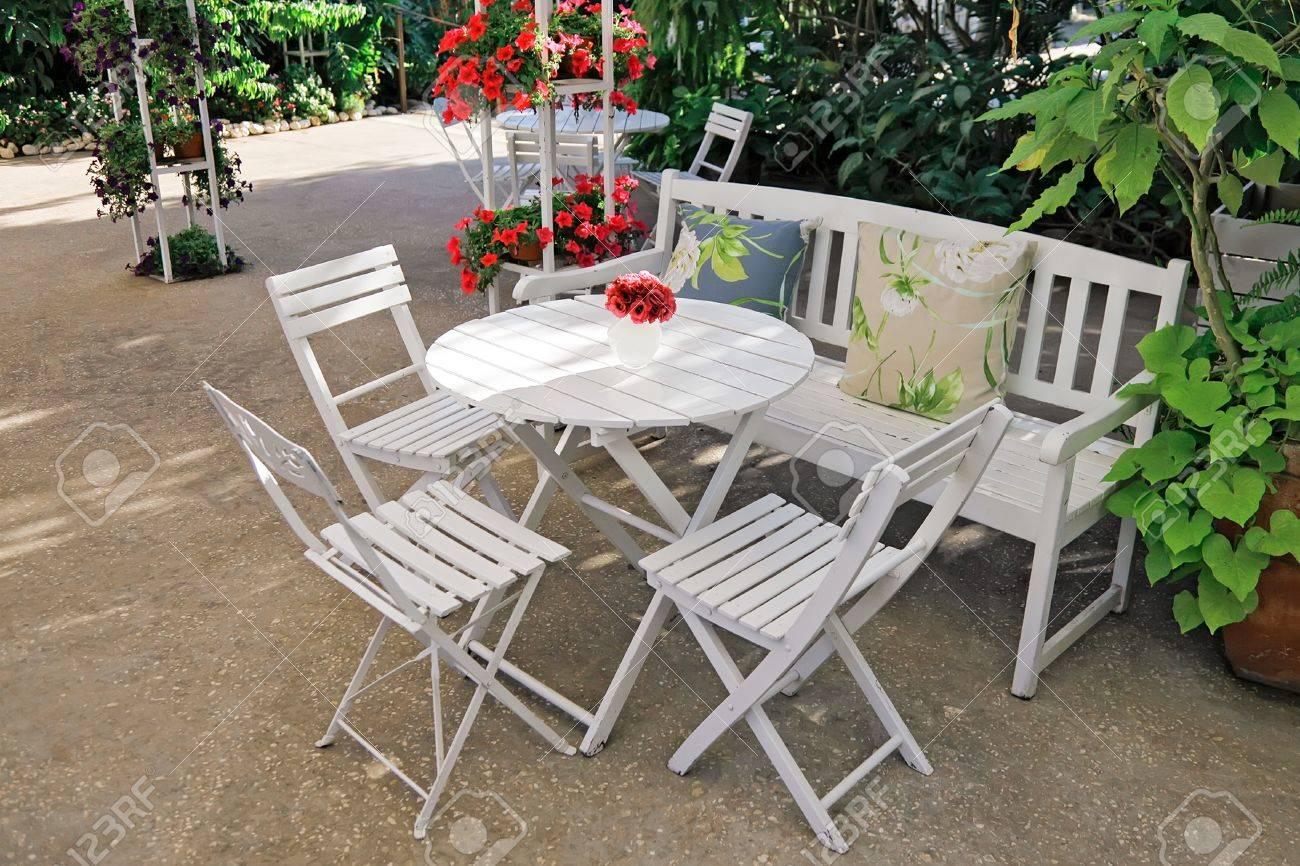 Standard Bild   Weißer Stuhl, Tisch, Bank Mit Kissen In Einem üppigen Garten