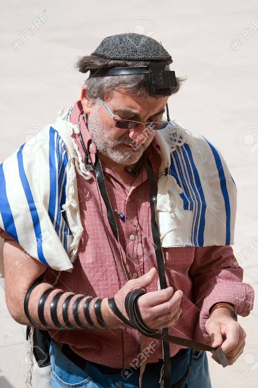 Jerusalem, Israel - March 14, 2006  Praying men wearing a tallith and tefillin at the Wailing Wall in Jerusalem  The Western Wall, Wailing Wall or Kotel is located in the Old City of Jerusalem at the foot of the western side of the Temple Mount   Tefillin Stock Photo - 13047610