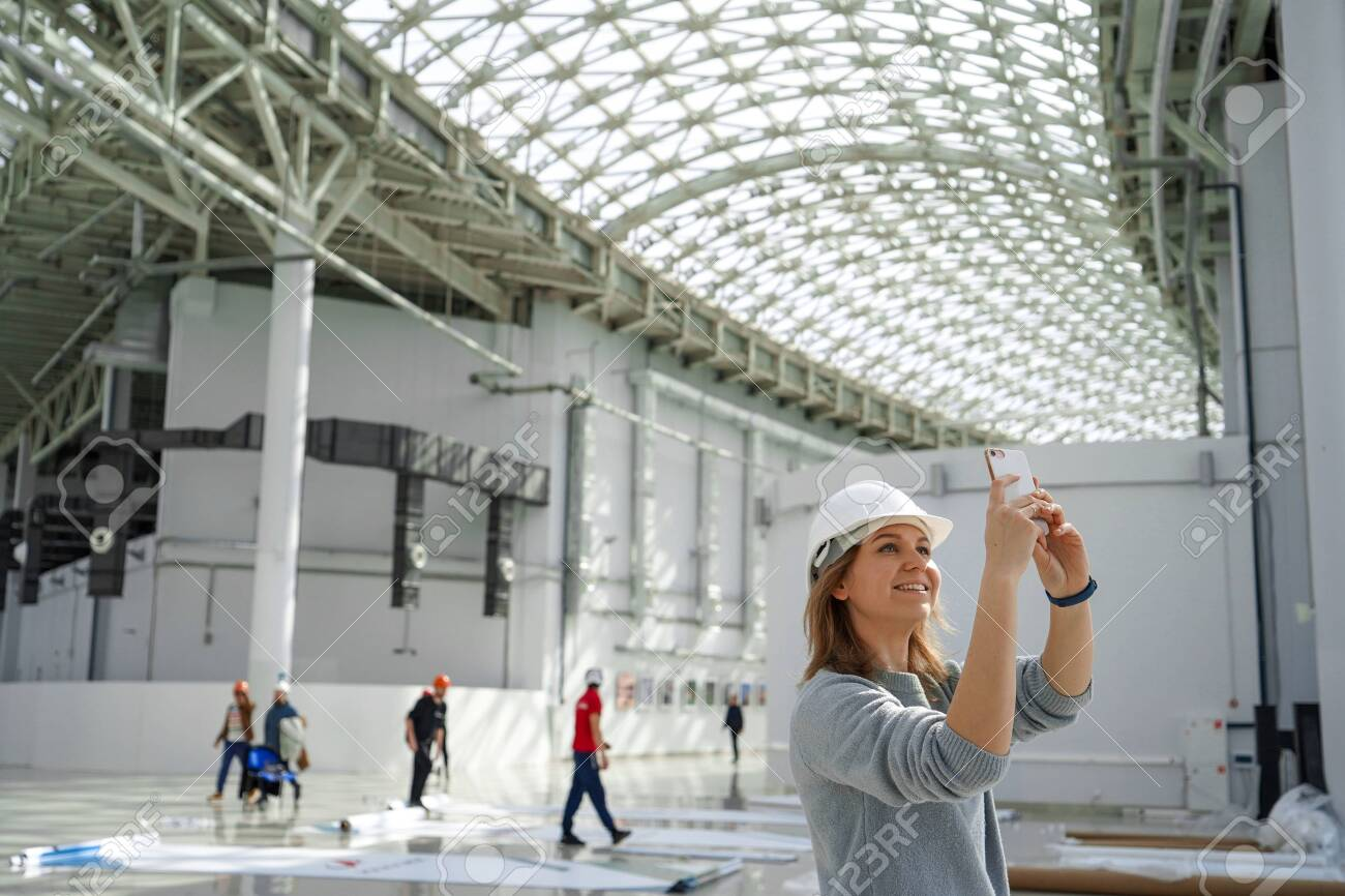 Young girl in a helmet takes pictures on the phone, in the background the workers, an excursion to the construction site, an engineer is satisfied - 127880851