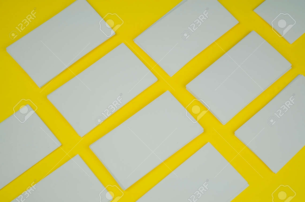 many blank white mokap business cards on a yellow background - 160849409