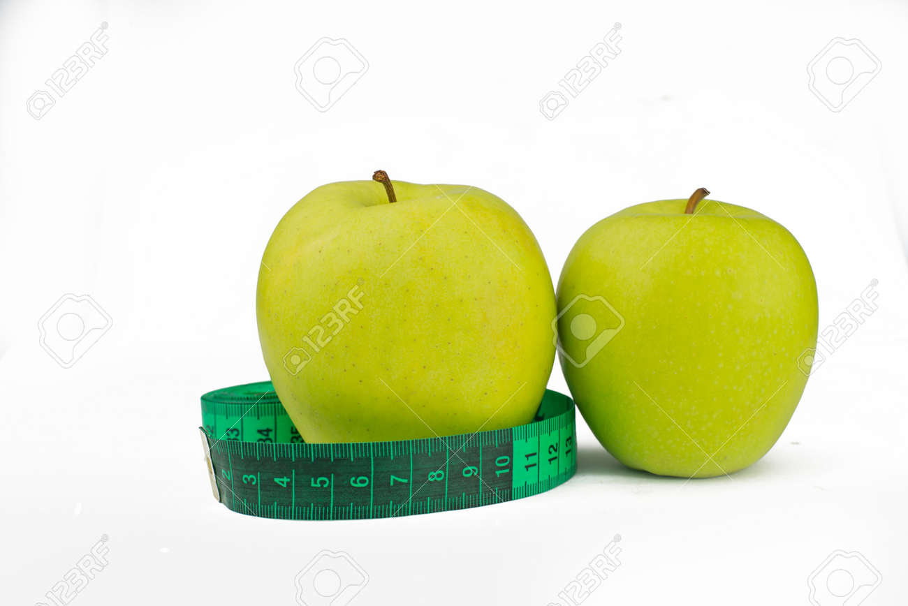 green apples with measuring centimeter for weight control and health and diet on a white background - 163505585