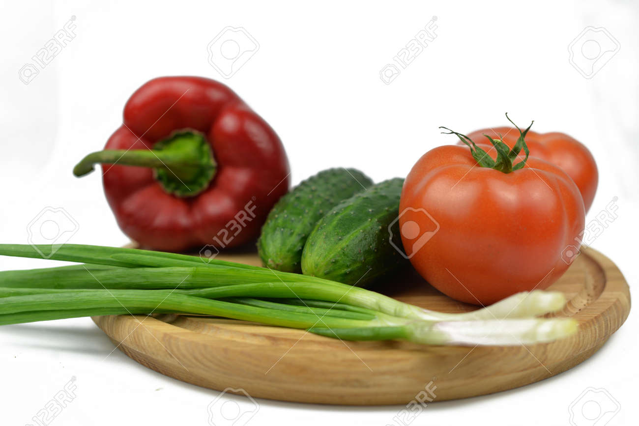 board on a wooden board vegetables with green onions tomatoes red paprika peppers green cucumbers and diet vitamins on a white isolated background - 163505590