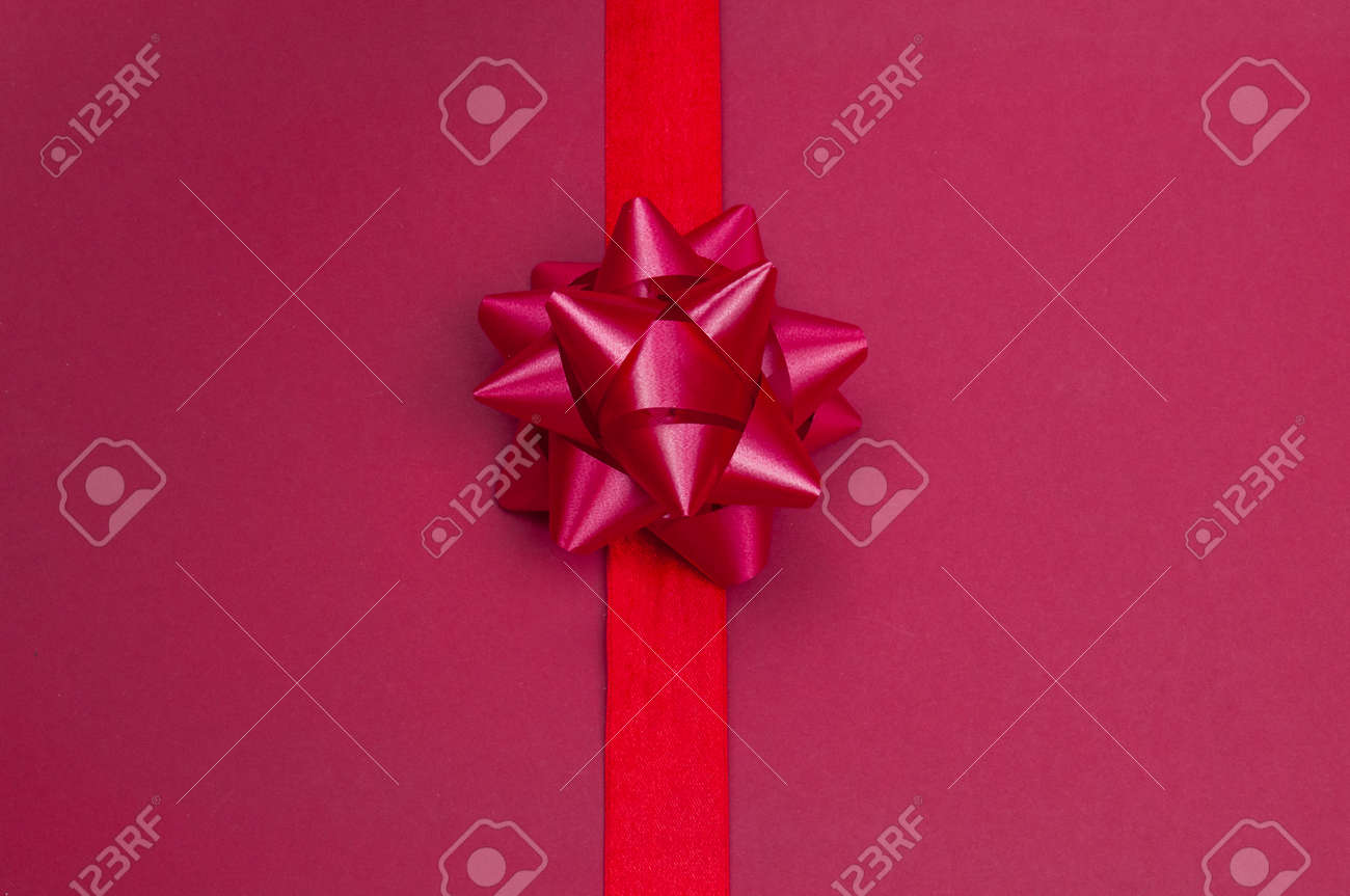 elegant festive knotted bow ribbon for gift red on isolated pink background for valentine's day and new year - 162659315