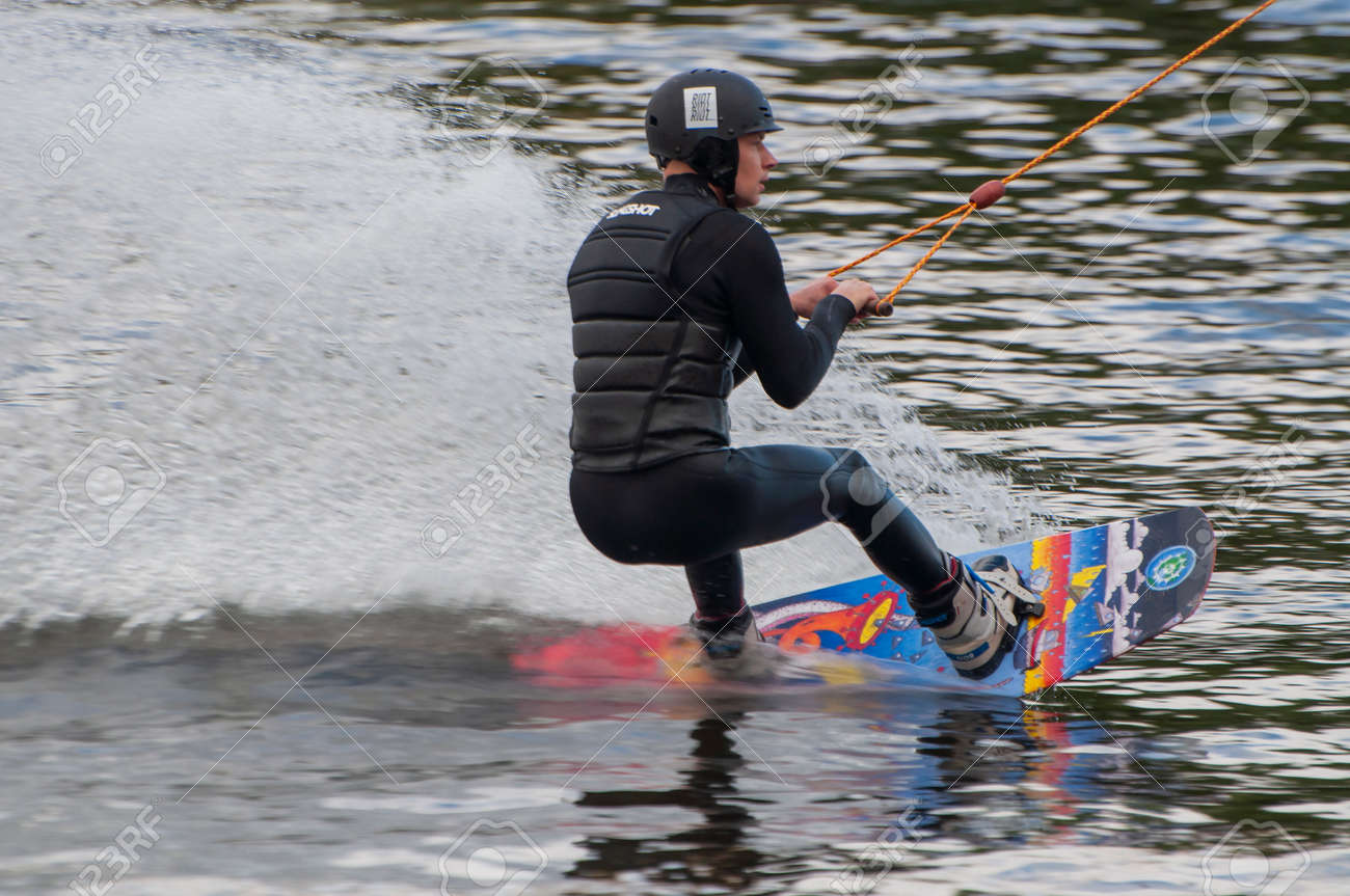 Kiev Ukraine - May 14, 2021, a guy, a man, an athlete rides and trains on the water as a sport Wakeboarding in the recreation area x - park - 171121878