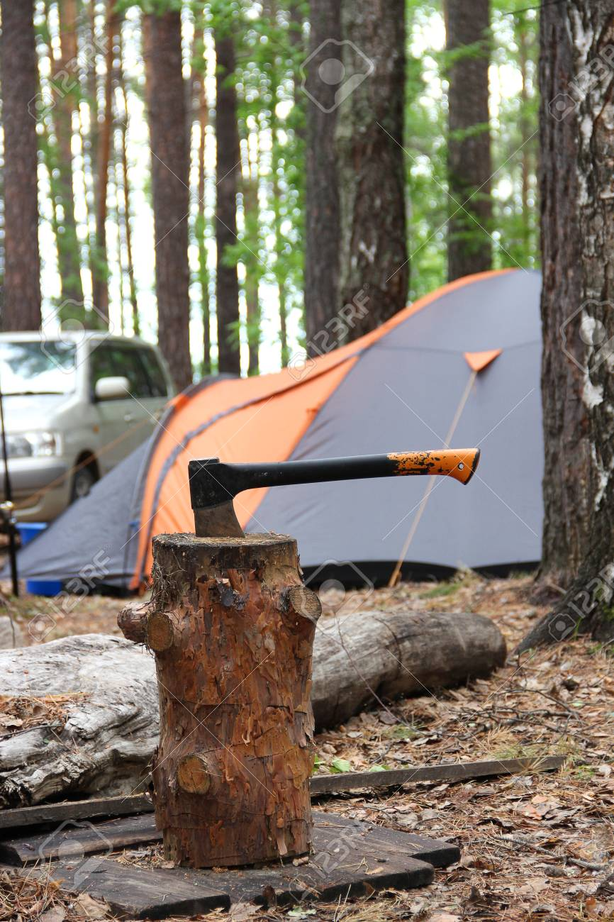 Black orange axe in the wooden stump on the background of tent and car in the & Black Orange Axe In The Wooden Stump On The Background Of Tent ...