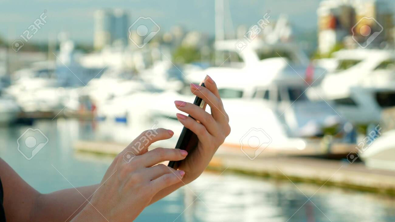female hand holds smartphone on blurred background of port with..