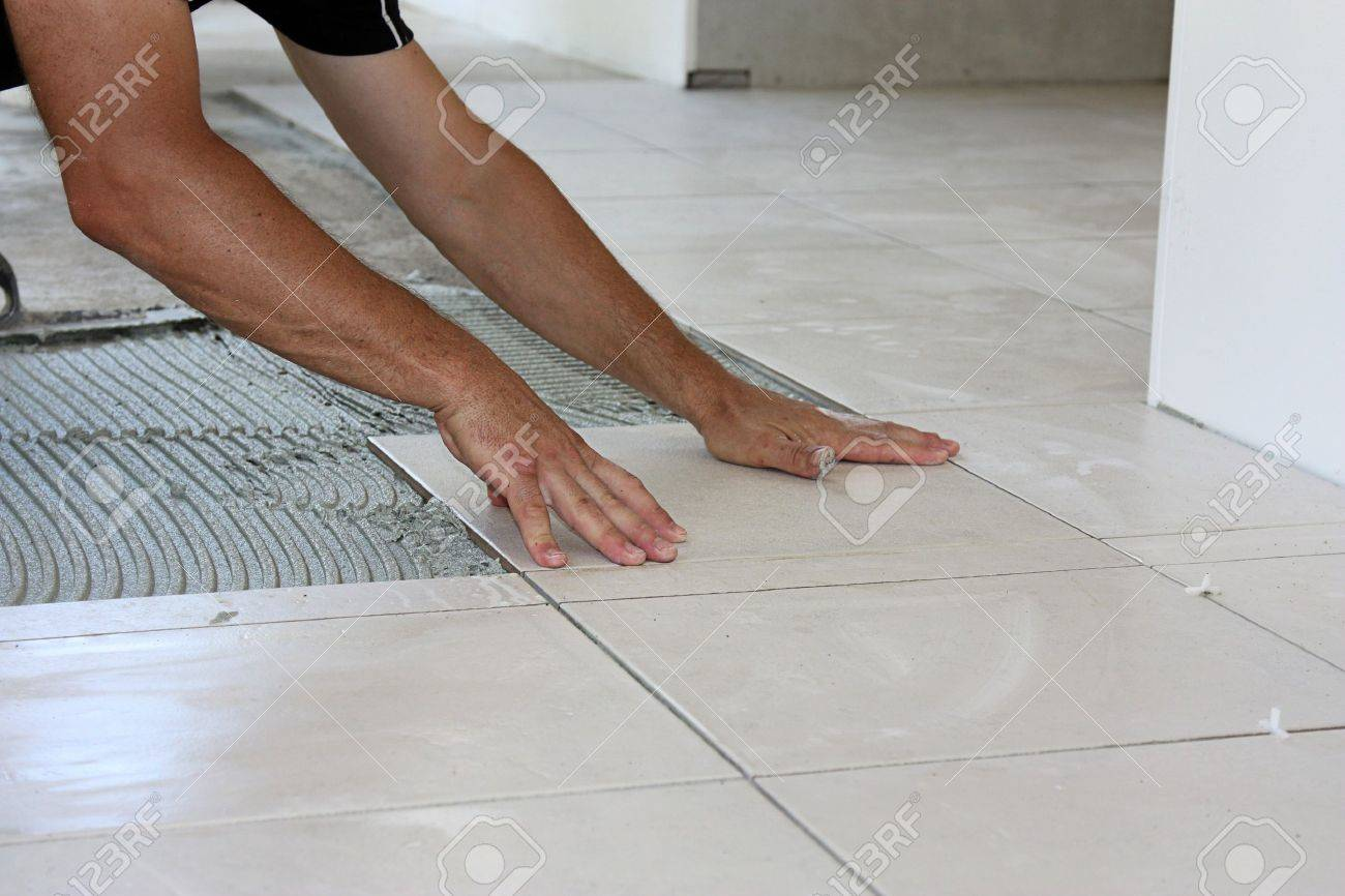 A male tiler laying light color floor tiles stock photo picture and a male tiler laying light color floor tiles stock photo 19433269 dailygadgetfo Gallery