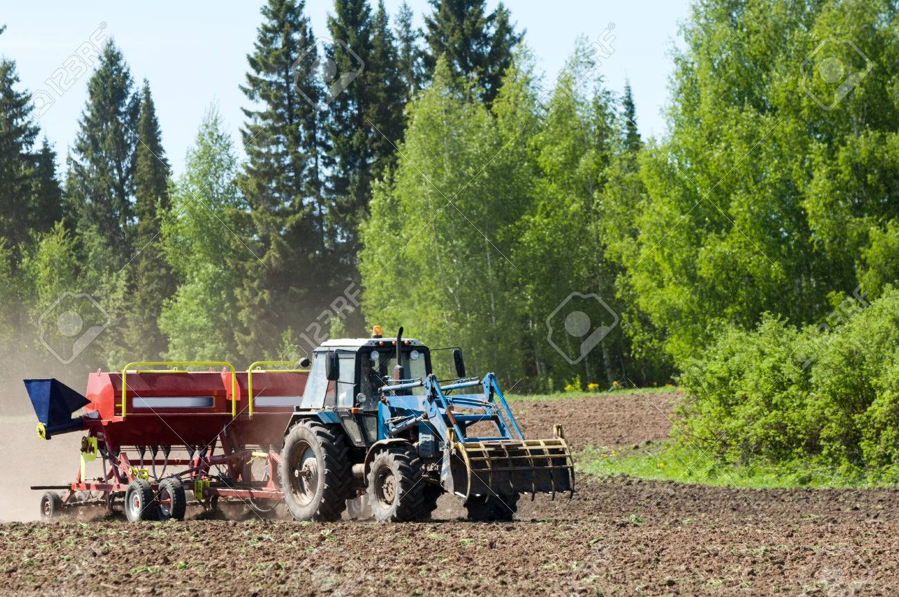 Tractor in the field  Tractor at the seed  Tractor working on the field  Tractor sowing seed  Ploughing heavy tractor during cultivation agriculture works at field with plough Stock Photo - 23137632