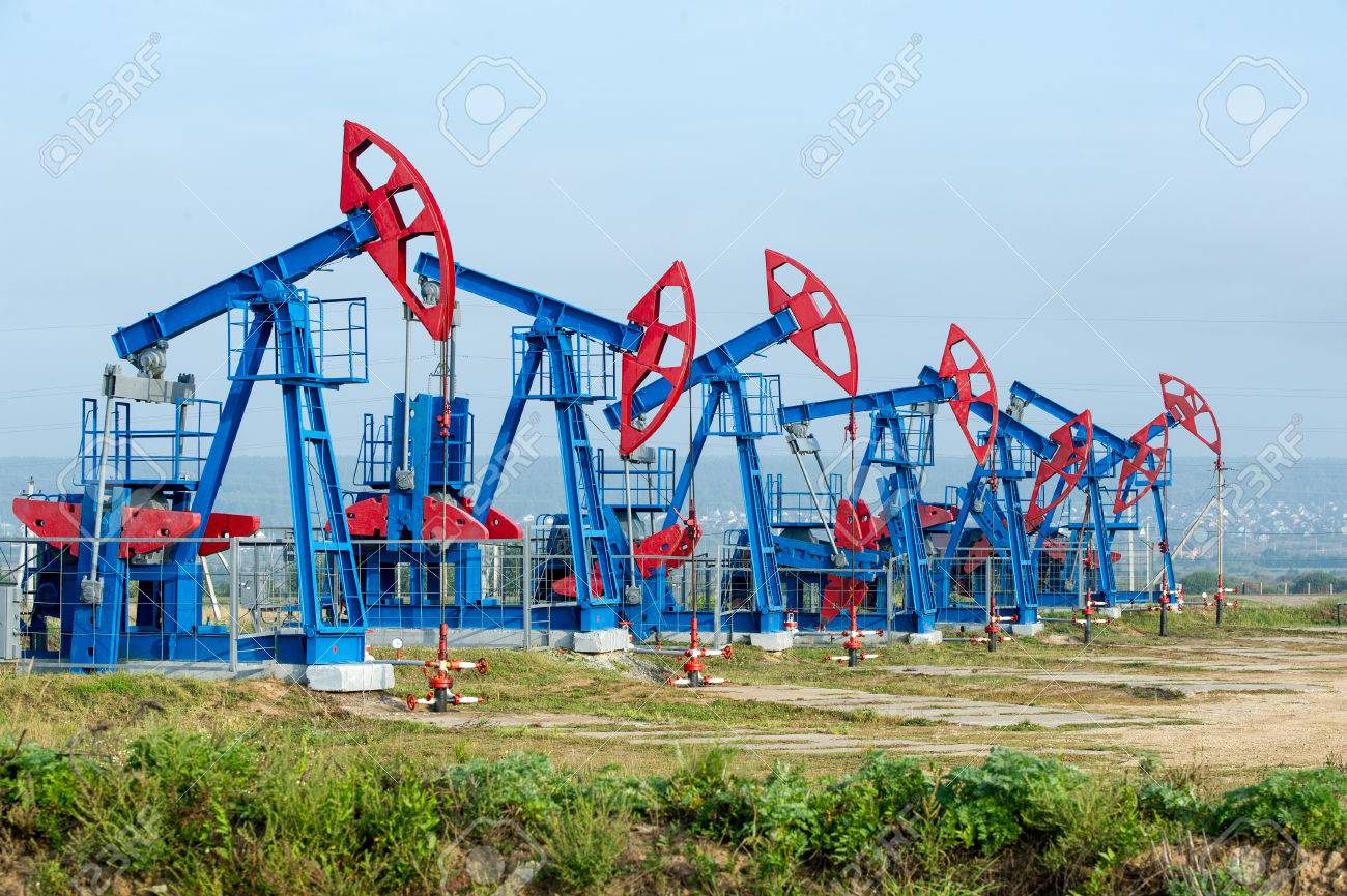 Oil and gas industry. Work of oil pump jack on a oil field. White clouds and blue sky. oil well pump. Oil and gas industry. Work of oil pump jack on a oil field. Stock Photo - 38830855