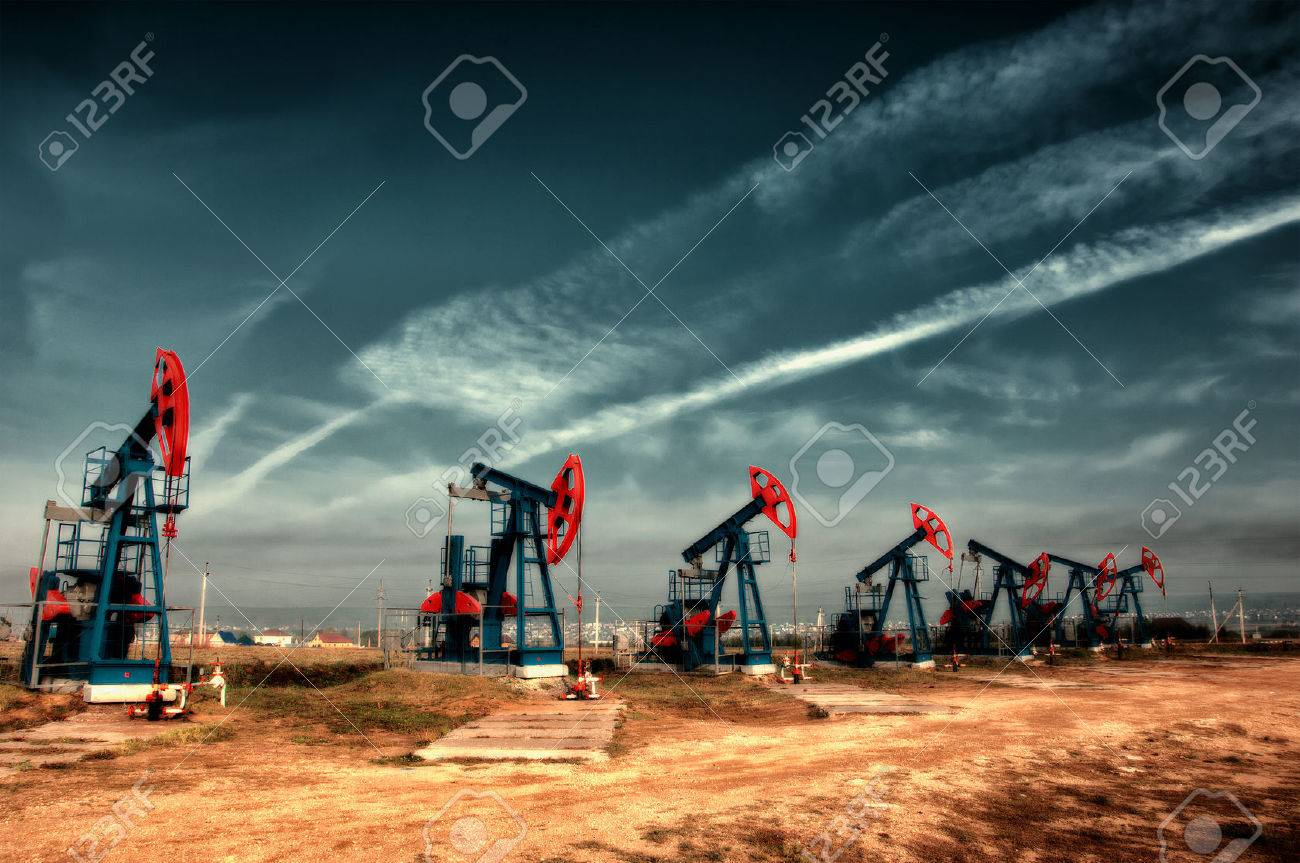 Oil and gas industry. Work of oil pump jack on a oil field. White clouds and blue sky. oil well pump. Oil and gas industry. Work of oil pump jack on a oil field. Stock Photo - 38831163