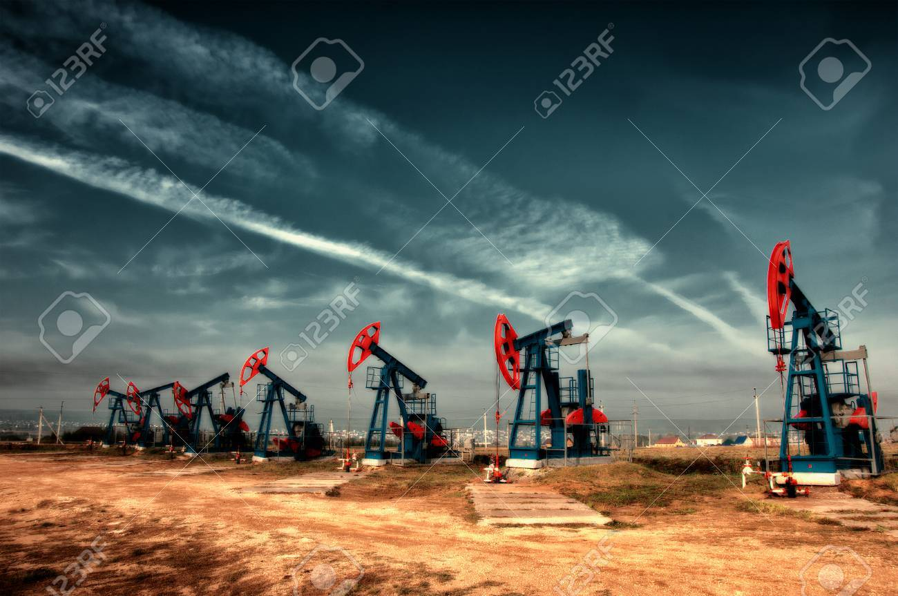 Oil and gas industry. Work of oil pump jack on a oil field. White clouds and blue sky. oil well pump. Oil and gas industry. Work of oil pump jack on a oil field. Stock Photo - 42355379