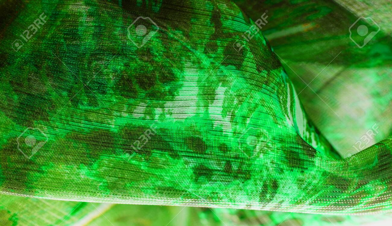 Background texture, pattern. Silk from a greenish emerald shade. This luxurious silk chiffon fabric is a show-stopper. It is clean, has a liquid drape and ultra soft. It is perfect for your design. - 138605298
