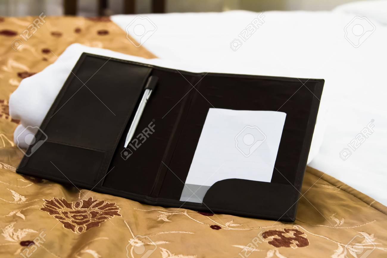 White blank note with pen on bed in hotel room. Stock Photo - 22721754