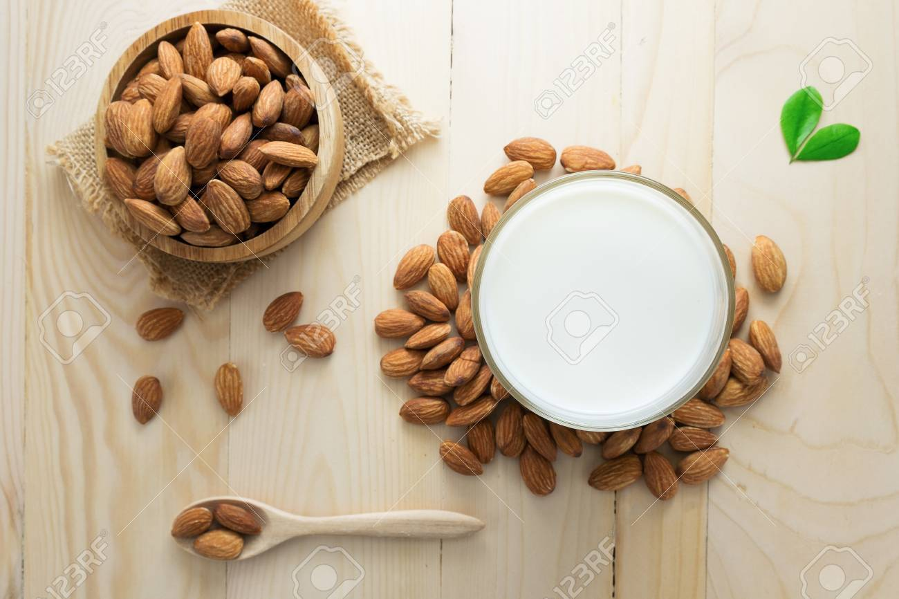 Almond milk in a glass with almonds. - 57564982