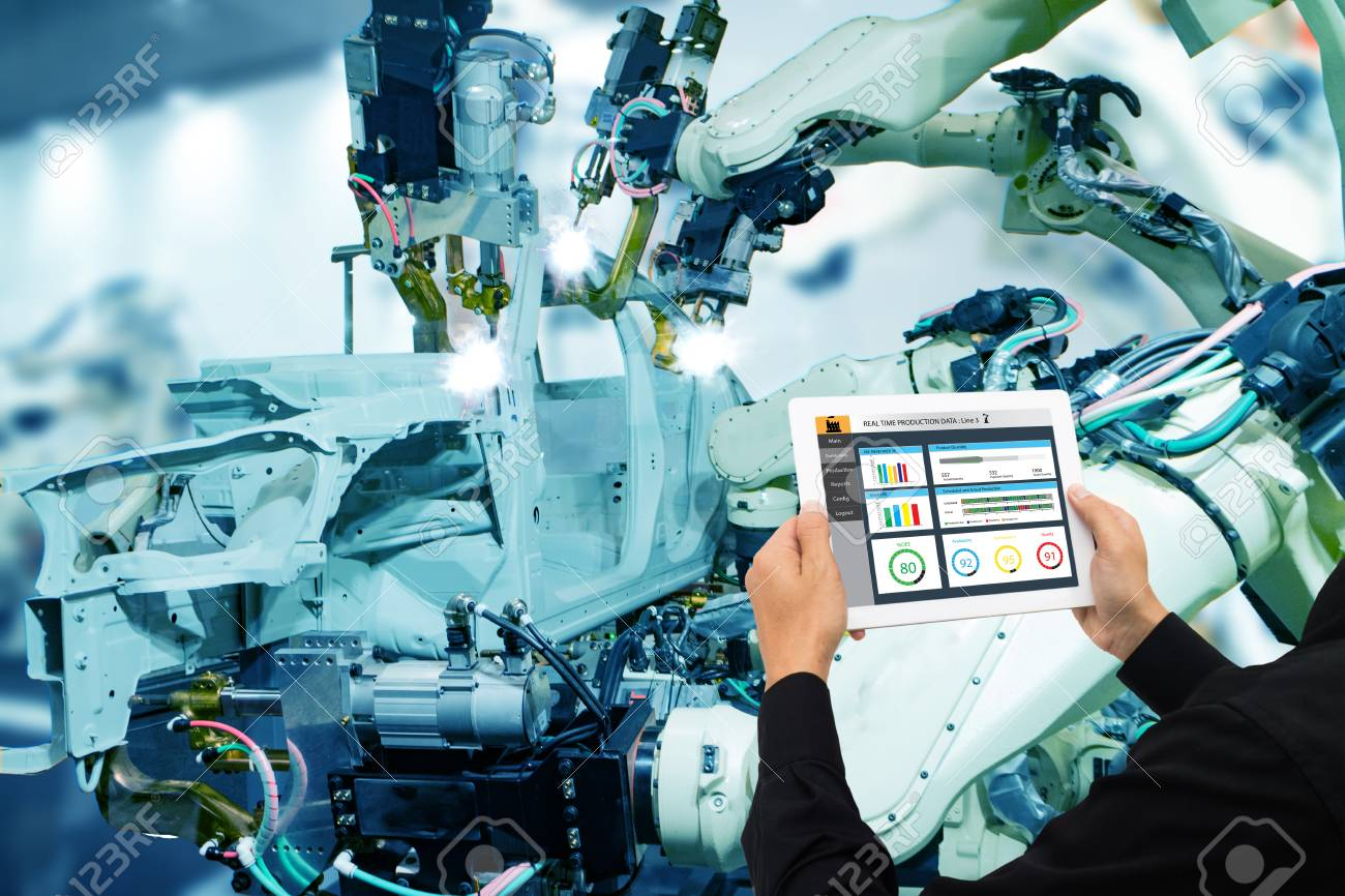 iot industry 4.0 concept,industrial engineer using software (augmented, virtual reality) in tablet to monitoring machine in real time.Smart factory use Automation robot arm in automotive manufacturing - 93708182