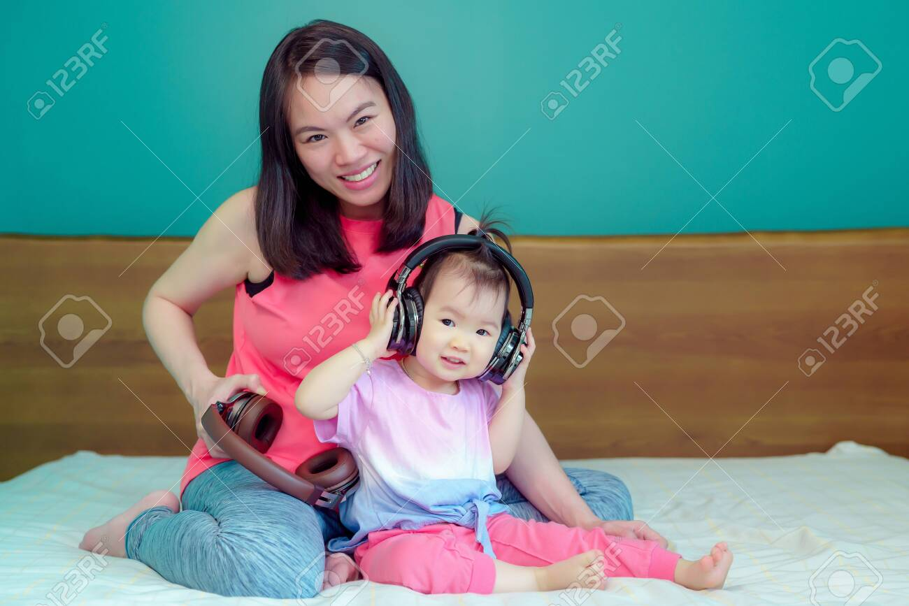 A beautiful Asian lady mother is pregnant. Take a big headset Come to the stomach Let the child in the belly listen Have a little daughter playing beside happily - 123616748